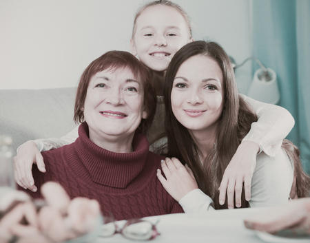Smiling grandmother with adult daughter and granddaughter hugging at home