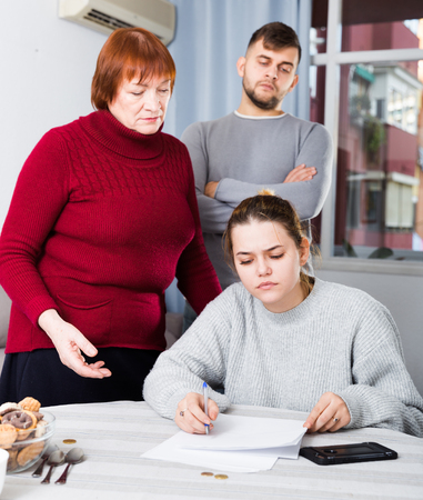 Frustrated young woman looking at papers on background with discontented husband and his mother