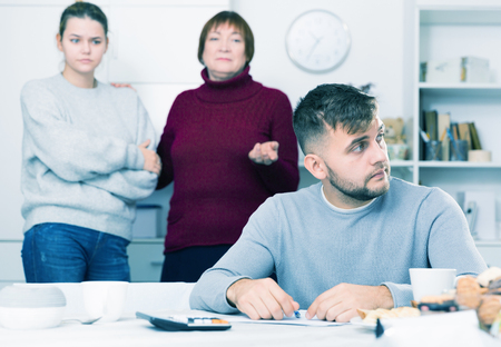 Upset guy sitting with documents while dissatisfied girl with older woman standing behind him