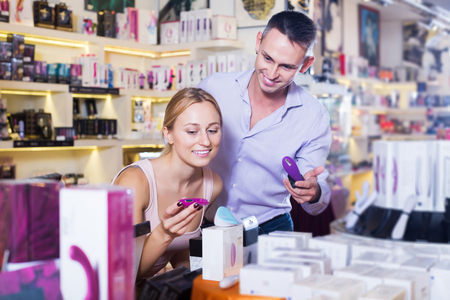 Portrait of smiling young couple choosing erotic toys in sex shop