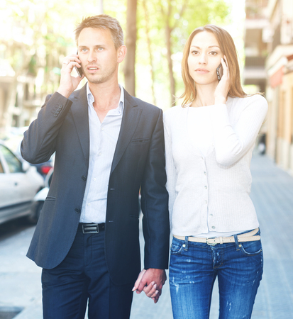 Indifferent girl and guy speaking on phones while walking together