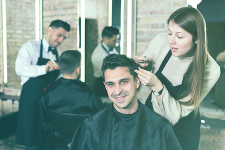 Handsome male client getting haircut by professional hairdresser in salon Banque d'images