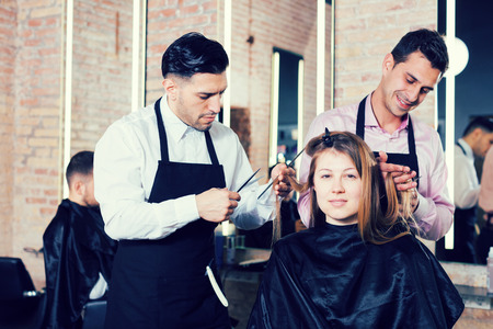 Attractive long-haired brunette getting haircutting from two professional hairstylists in salon Stock Photo