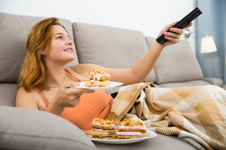 Positive woman on sofa with fresh cake and remote watching tv