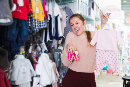 happy female buyer choosing clothes for infant in the dress shop for baby Stock Photo