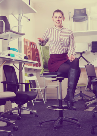 Attractive saleswoman in furniture salon demonstrating convenience of bar stool