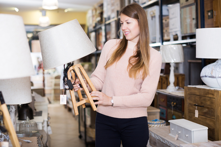Smiling young consumer choosing torchere in furniture shopping room Stock Photo