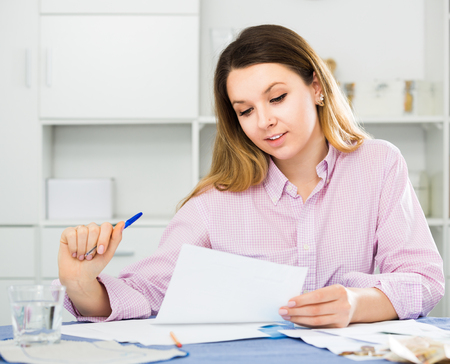 Positive young woman signing financial papers at home  Stock Photo