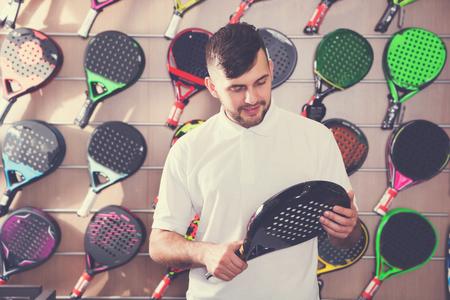 Smiling guy choosing racquet for padel in sport goods shop