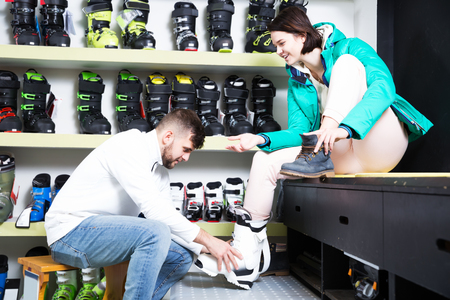 Cheerful young couple choosing ski boots for girl in sport goods shop. Focus on girl 스톡 콘텐츠