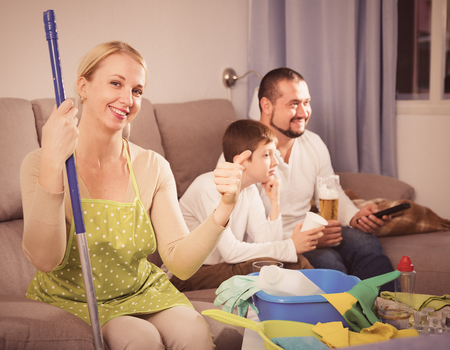 Smiling woman dressed for cleaning sitting on sofa while husband with son relaxing