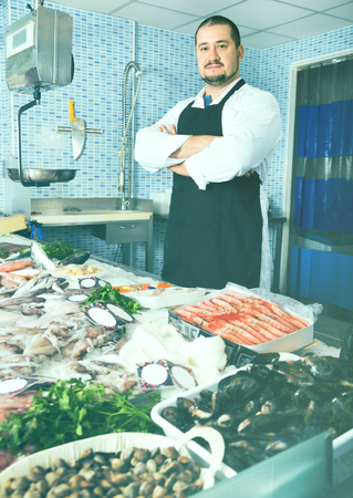 Glad  seller in black apron showing fish on his counter in supermarket