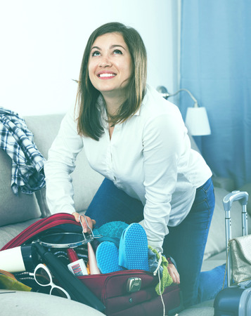 Young  positive girl starting packing luggage for journey at home Stok Fotoğraf