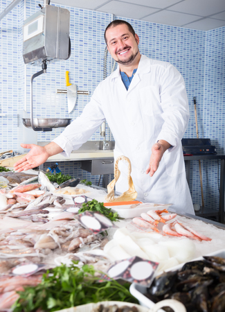 Adult positive man with beard arms folded standing near fish counter