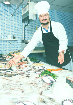 Standing laughing man in black apron shows the fish counter