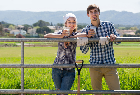 smiling young man and woman chatting and enjoying milk outdoors Stock Photo
