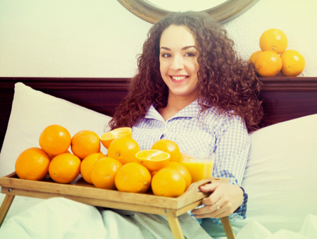 Adult girl posing with orange juice and fruits in bed