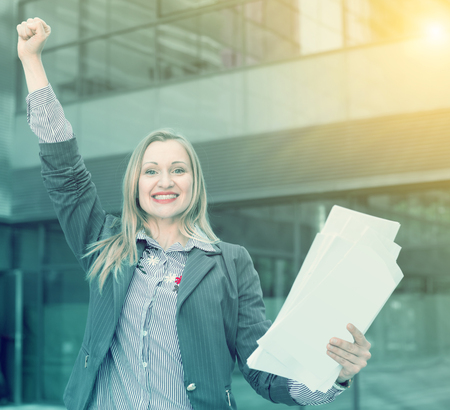Employee glad woman in suit standing with paper documents at the city