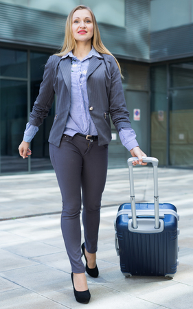 Portrait of cheerful female standing with bag at the modern city Stock Photo