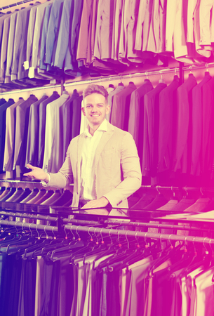 Cheerful male seller demonstrating numerous suits in men's cloths store