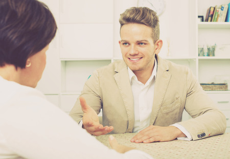 Young handsome man tells woman about interesting offers of his company Stock Photo