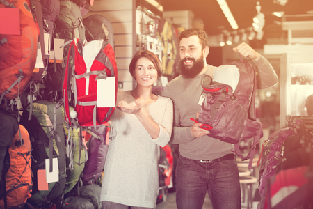 Young guy and a girl choose a big backpack in a store for sports Stock Photo