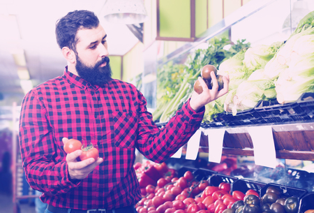 Positive man seller offering tomatoes in grocery shop