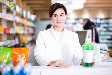 Adult pharmacist ready to assist in choosing at counter in pharmacy