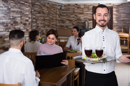 Portrait of adults guest in middle class restaurant and young waiter Archivio Fotografico