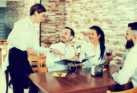 Glad waitress taking order at table of people having dinner together