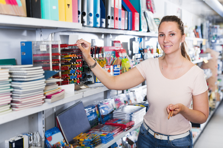 Portrait of young woman choosing color pencil in stationery shop