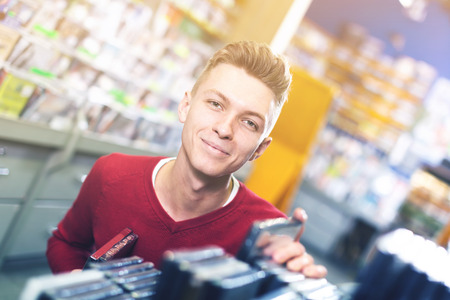 Smiling man looking for interesting movies on shelves of CD shop Stock Photo