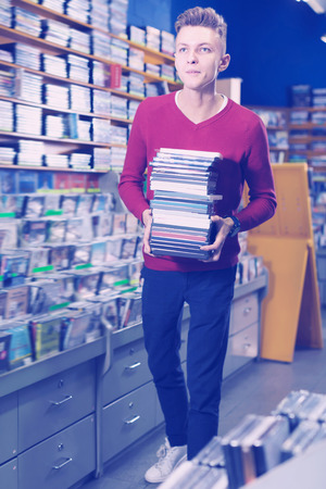 Young man bearing pile of discs in cases during shopping in CD store Stock Photo