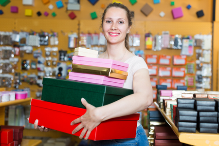 Girl is demonstration colored boxes in shop.  Stock Photo