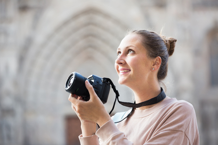 Cheerful woman  taking picture with camera in the town