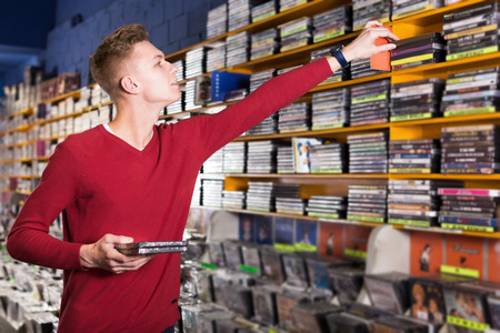 Serious young man absorbedly choosing CD and DVD in shop  Stock Photo
