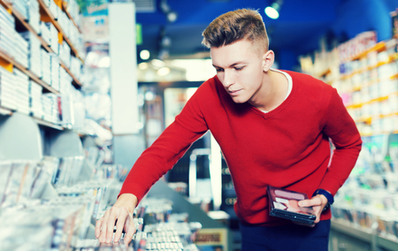 glad handsome focused young guy looking for interesting movies on shelves of CD shop
