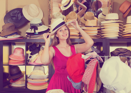 Happy  young blonde woman choose natural hat in shop