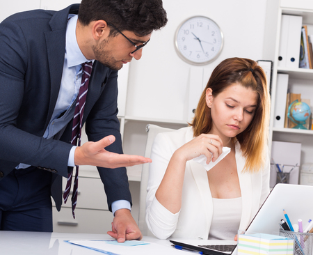 Angry boss blowing up female subordinate for mistakes in work