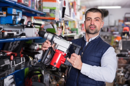 Confident man is choosing drilling machine in tools shop