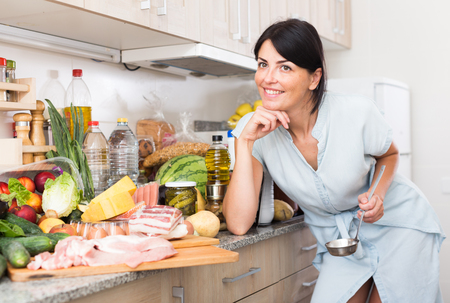Cheerful woman is posing in time cooking on the kitchen at home.