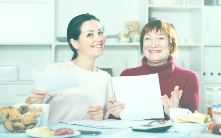 Portrait of mature woman and daughter with documents at table with food Stock Photo
