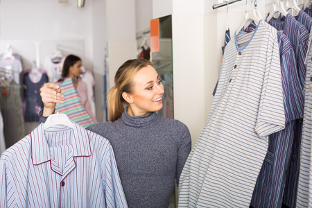 Smiling young woman choosing pajamas top for man in shop with underclothing  Banco de Imagens