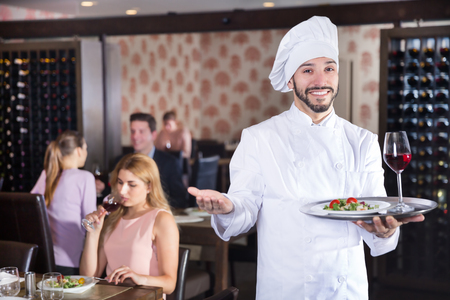 Portrait of confident smiling chef standing with serving tray at the restaurant  Stok Fotoğraf