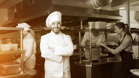 Confident chef of restaurant posing in kitchen on background with employees