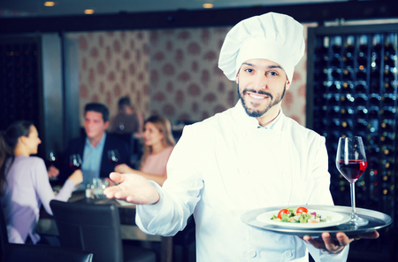 Handsome young chef with dishes on serving tray welcoming to restaurant