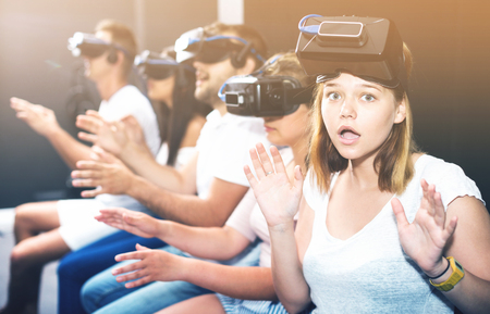 Portrait of frightened young girl after watching of exciting movie with VR glasses in entertainment room.