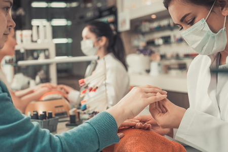 Nail masters performing manicure and massage in beauty salon Stock Photo