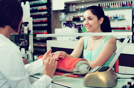 Manicure masters performing manicure and massage procedures in nail salon