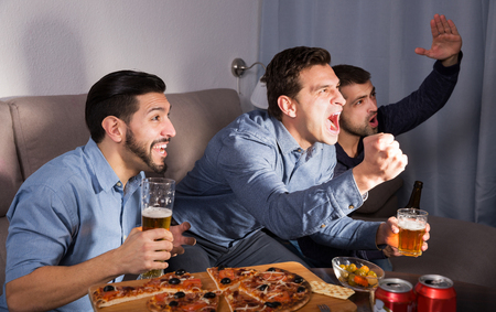 Exalted male friends watching tv together at home, enjoying beer and pizza at home
